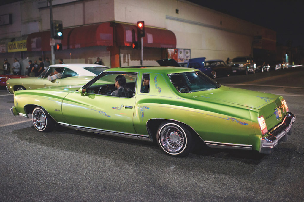 A green lowrider moves down the street.