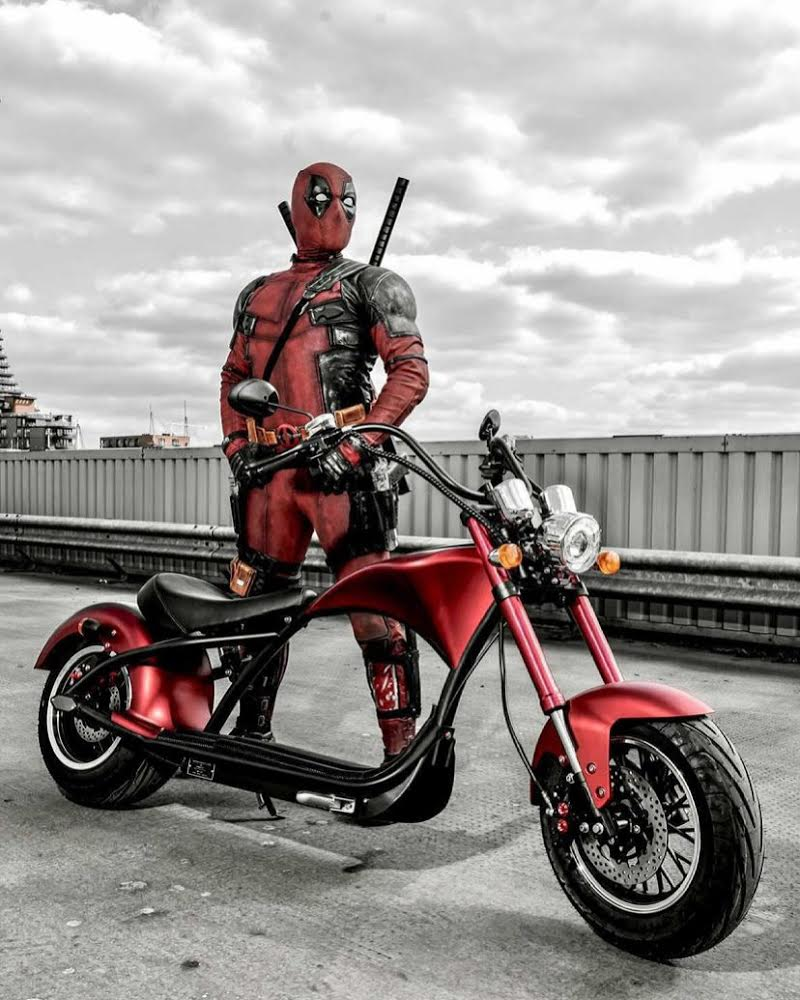 Someone dressed as Deadpool stands near a Sterling Eco bike