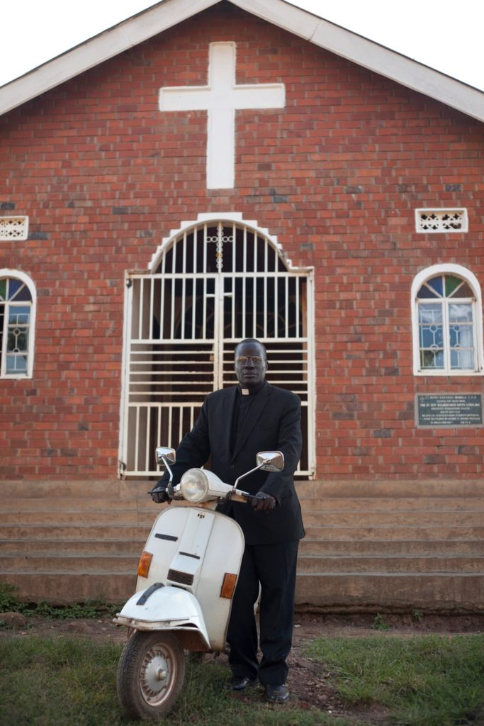 A reverend outside his place of worship - with his Vespa