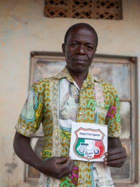 A member of the Vespa Club Uganda shows off their badge