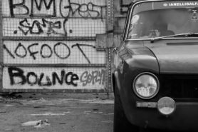 The Alfa sits in front of a graffiti-adorned wall