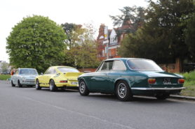 Three 'Wacky Racers' cars lined up on the side of a street